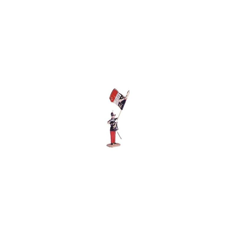 """Porte drapeau au garde à vous. On peut lire sur le drapeau : """"Ils s'instruisent pour vaincre""""."""